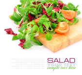 Fresh mixed salad with tomatoes on a wooden board — Stok fotoğraf