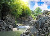 Tranquil waterfall with rocks by a summer — Stock Photo