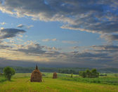 Beautiful sky is after sunset of a sun and summer meadow with haycocks — Stock Photo