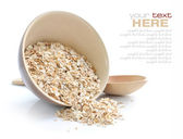 Oat flakes in bowl and wooden spoon on white background — Stock Photo