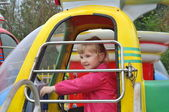 Little girl on carousel rides in the park — Stock Photo
