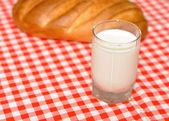 Ett glas mjölk och en limpa av vete — Stockfoto