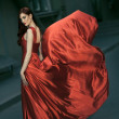 Stock Photo: Sexy young beauty woman in fluttering red dress