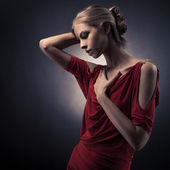 Young beautiful woman in red dress on the dark background in the — Stock Photo