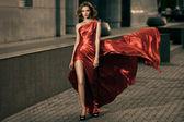 Mulher de beleza jovem sexy em esvoaçantes vestido vermelho — Foto Stock
