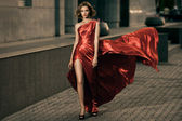 Sexy young beauty woman in fluttering red dress — Стоковое фото