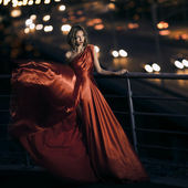 Sexy young beauty woman in fluttering red dress — Stok fotoğraf