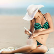 Portrait of woman taking skincare with sunscreen lotion at beach — Stock Photo