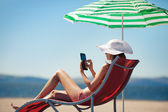 Woman holding tablet computer sitting on the beach in deck chair — Stock Photo