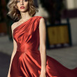 Sexy young beauty woman in fluttering red dress — Stock Photo