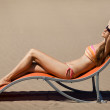 Beautiful woman lying on a deckchair at the beach — Stock Photo #11705414