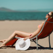 Stock Photo: Beautiful woman lying on a deckchair at the beach