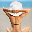 Bright photo of a beautiful model relaxing on a beach. Room for — Stock Photo #12143579