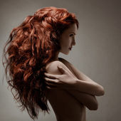 Beautiful woman with curly hairstyle against gray background — ストック写真