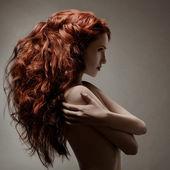 Krásná žena s kudrnatý účes šedé pozadí — Stock fotografie