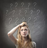 Young woman with doubtful expression and question marks over her head — Stock Photo
