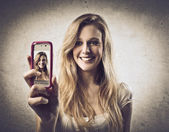 Young woman taking photos with a mobile phone — Stock Photo