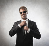 Handsome young businessman adjusting his tie — Stock Photo