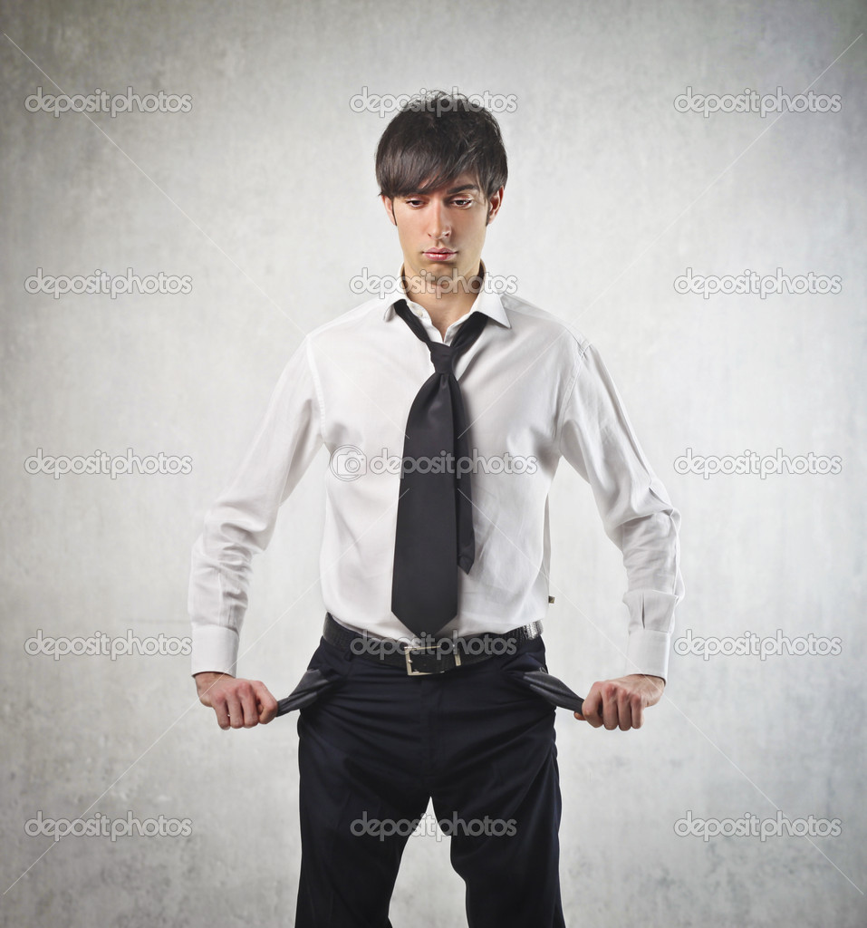 Sad young businessman turning his pockets inside out — Stock Photo #10761637