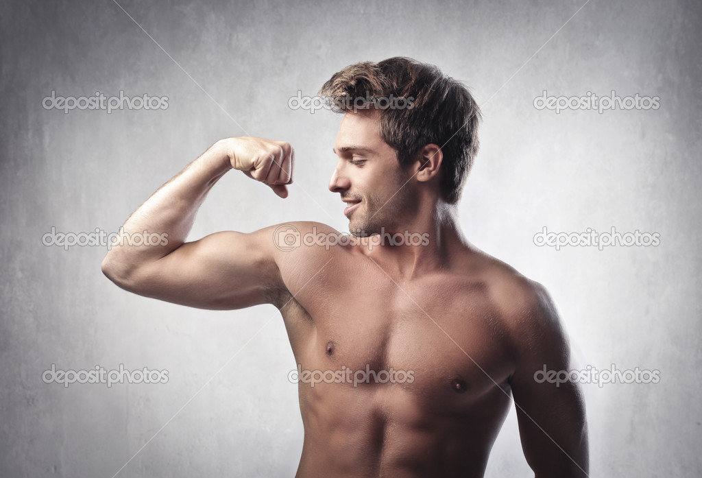 Smiling handsome young man showing his biceps — Stock Photo #10761916
