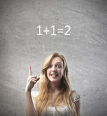 Smiling young woman finding the solution to the easy calculation over her head — Stock Photo