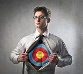 Young businessman showing a target under his shirt — Stock Photo