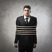 Young businessman tied with ropes — Stock Photo