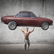 Muscular man holding a car in his hands — Stock Photo