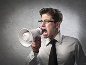 Young businessman screaming into a megaphone — Stock Photo