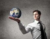 Young businessman holding the Earth in his hand [Elements of this image furnished by NASA] — Stock Photo