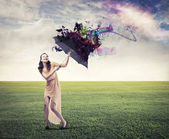 Laughing beautiful woman on a green meadow sheltering from the rainbow under an umbrella — Stock Photo
