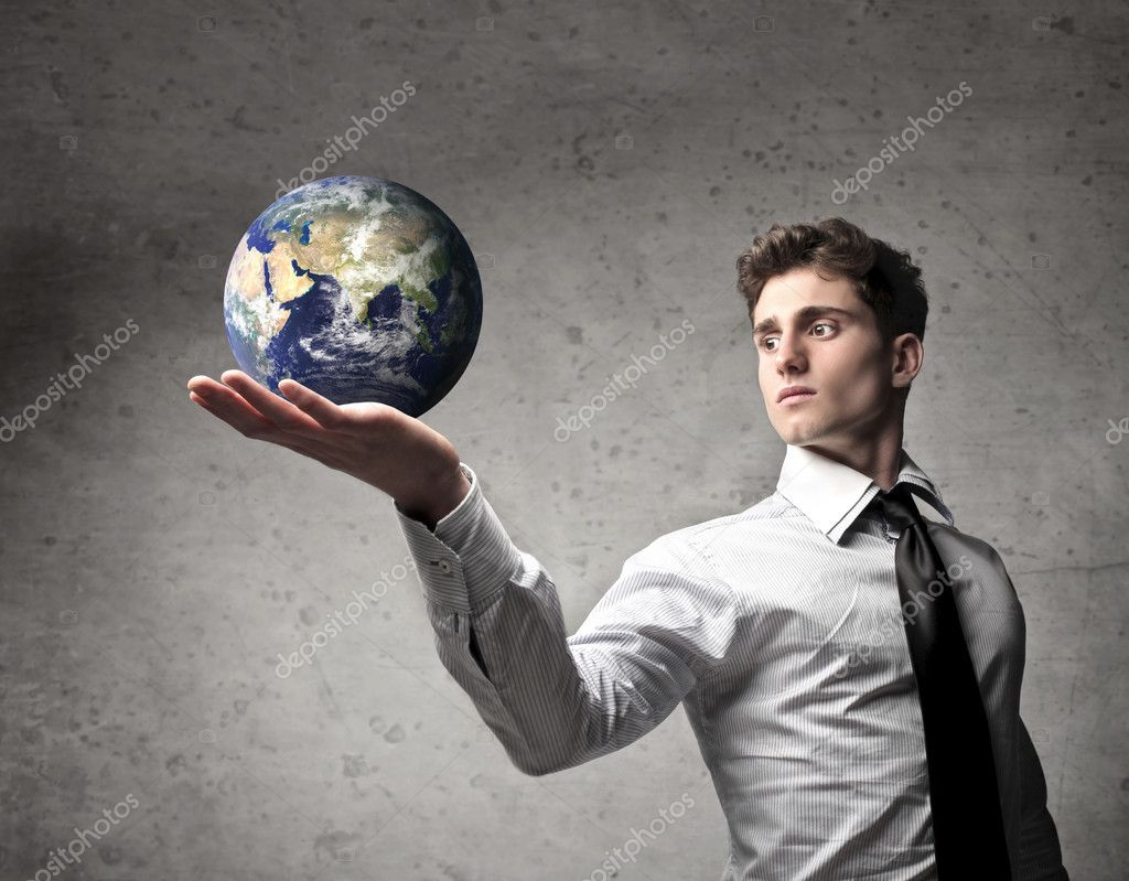 Young businessman holding the Earth in his hand [Elements of this image furnished by NASA] — Stock Photo #10911416