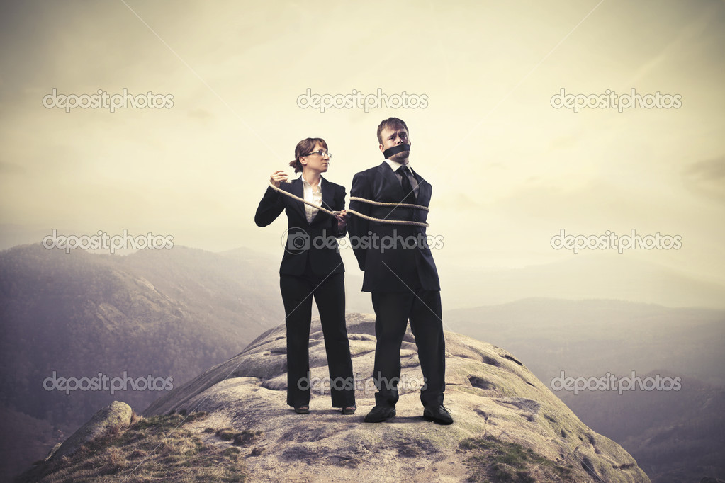 A businessman is a hostage on a high cliff.  Stock Photo #11396545