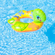 Child's green rubber ring in swimming pool — Stock Photo