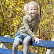 Little girl sitting on bench in spring — Stock Photo #10764704