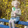 Little girl with a lollipop sitting on bench in spring — Stock Photo