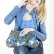 Portrait of sitting woman with mobile phone and handbag — Stock Photo