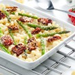Pasta baked with dried tomatoes, asparagus and pecorino cheese — Stock Photo #10986497