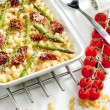Pasta baked with dried tomatoes, asparagus and pecorino cheese — Stock Photo #10986501