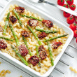 Pasta baked with dried tomatoes, asparagus and pecorino cheese — Stock Photo #10986503