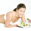 Stock Photo: Lying down womeating salad