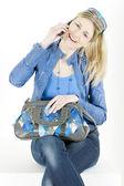 Portret van zittende vrouw met mobiele telefoon en handtas — Stockfoto