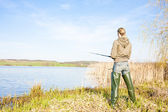 Woman fishing at a pond — Stock Photo