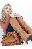 Portrait of sitting woman wearing fashionable brown boots with a handbag — Stock Photo