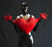 Woman in latex with heart — Stock Photo
