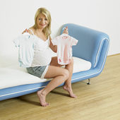 Pregnat vrouw met kleren voor baby 's — Foto de Stock