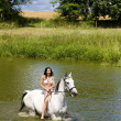 Equestrian on horseback riding through water - Stock Photo