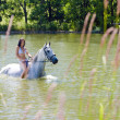 Equestrian on horseback riding through water — Stock Photo #11284112