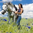 Stock Photo: Equestrian with a horse on meadow
