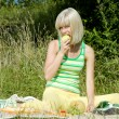Woman with apple at a picnic — Stock Photo